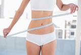 Close up of a slender woman measuring her waist