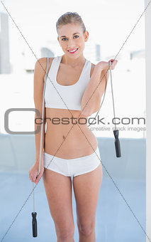 Cheerful young blonde model playing with a skipping rope