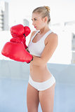 Concentrated young blonde model exercising with boxing gloves