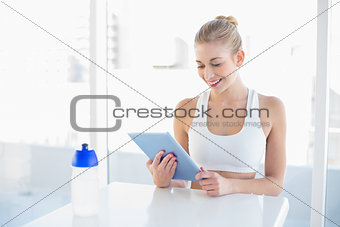 Attractive young blonde model using a tablet pc