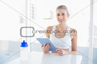 Charming young blonde model using a tablet pc