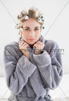 Lovely relaxed blonde woman in hair curlers looking at camera
