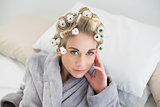 Thinking relaxed blonde woman in hair curlers looking at camera