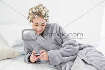 Happy relaxed blonde woman in hair curlers using her mobile phone