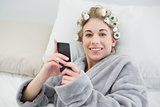 Charming relaxed blonde woman in hair curlers using her mobile phone