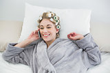 Delighted relaxed blonde woman in hair curlers making a phone call