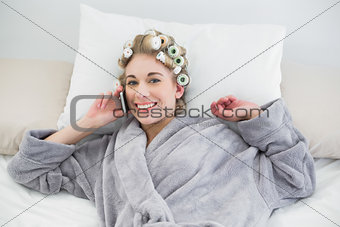 Cute relaxed blonde woman in hair curlers calling with her mobile phone