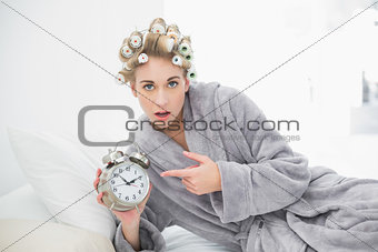 Astonished blonde woman in hair curlers pointing her alarm clock
