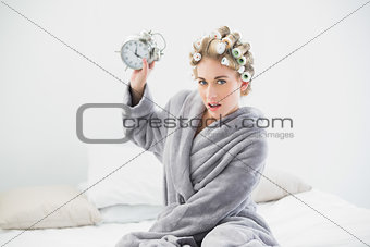 Angry blonde woman in hair curlers throwing her alarm clock