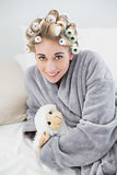 Happy relaxed blonde woman in hair curlers cuddling a plush sheep