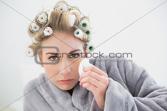 Troubled blonde woman in hair curlers crying and using tissues