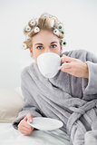 Charming blonde woman in hair curlers enjoying a cup of coffee