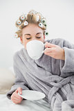 Cute relaxed blonde woman in hair curlers enjoying a cup of coffee