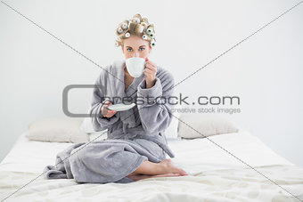 Attractive relaxed blonde woman in hair curlers drinking coffee