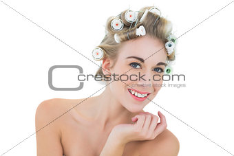 Pleased blonde model in hair curlers looking at camera