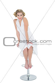 Joyful fashion blonde model sitting on bar chair