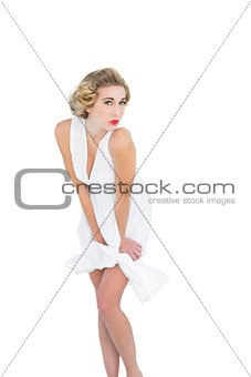 Seductive fashion blonde model posing holding her dress