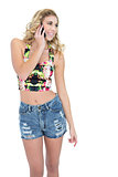 Amused retro blonde model calling with her mobile phone