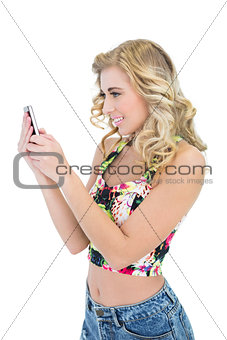 Joyful retro blonde model looking at her mobile phone