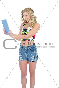 Charming retro blonde model looking at a tablet pc