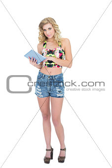 Thoughtful retro blonde model holding a tablet pc