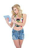 Thinking retro blonde model looking at a tablet pc