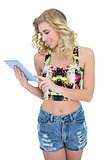 Happy retro blonde model looking at a tablet pc
