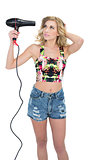 Concentrated retro blonde model using a hair dryer