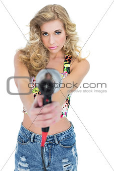 Unsmiling retro blonde woman pointing a hair dryer to the camera