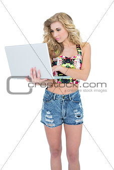 Concentrated retro blonde model using a laptop