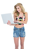 Pleased retro blonde model using a laptop