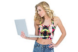 Thoughtful retro blonde model using a laptop