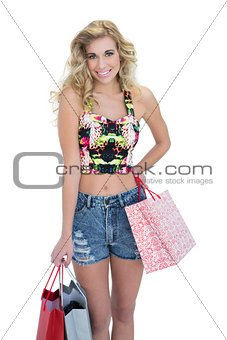Amused retro blonde model carrying shopping bags