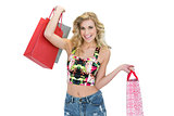 Joyful retro blonde model carrying shopping bags