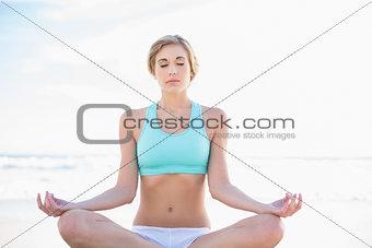 Peaceful blonde woman in sportswear practicing yoga