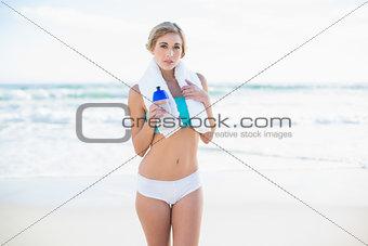 Calm blonde woman in sportswear holding a bottle of water