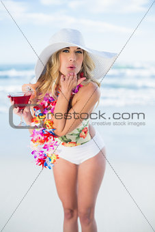 Cheerful blonde model in swimsuit blowing a kiss to the camera