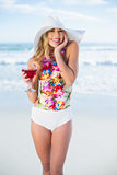 Pleased blonde model in swimsuit holding a cocktail