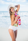 Joyful blonde model in swimsuit holding a cocktail