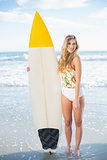Smiling blonde model in swimsuit standing next to a surfboard