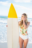 Pensive blonde model in swimsuit holding a surfboard