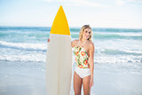 Amused blonde model in swimsuit holding a surfboard