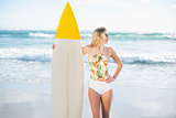 Thoughtful blonde model in swimsuit holding a surfboard