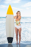 Charming blonde model in swimsuit holding a surfboard