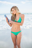 Pensive blonde model in green bikini using a tablet pc