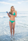 Cheerful blonde model in green bikini holding a tablet pc