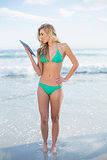 Smiling blonde model in green bikini looking at a tablet pc
