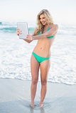 Delighted blonde woman in green bikini holding a tablet pc
