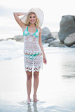 Pleased blonde woman in white beach dress posing looking at camera