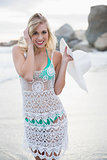Cheerful blonde woman in white beach dress holding her hat